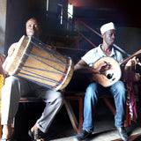 Colour photograph of two Comorian musicians sat playing their instruments ; they are indoors in a bank of seats, but sat where the sun shines on them.