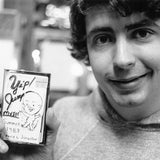 Black and white photograph of Daniel Johnston holding a cassette copy of Yip/Jump Music