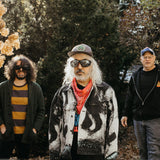Lou Barlow, J Mascis and Murph from Dinosaur Jr stood outdoors in the sun in front of some trees. They seem happy and are looking at the camera