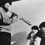 Black and white photograph of Evan Parker playing a saxophone towards two small children who hold fingers in their ears