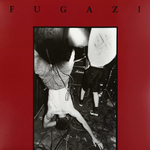 Fugazi's self-titled debut mini-album on Dischord Records (the album cover features a black and white live photograph by Adam Cohen of Guy Picciotto falling or standing on his head. This photograph is against a solid red background with the band name printed in an uppercase serif font across the top)