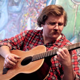 Colour photograph of Joseph Allred playing a 12-string acoustic guitar and wearing a red-check shirt; on their face they sport a moustache and thin-rimmed glasses, and they are looking at their fingers on the neck of the guitar.