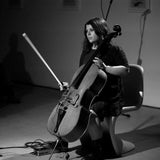 Black and white photograph of Judith Hamann playing live. Hamann is sat on a stylish chair, staring at the audience off camera, holding a cello with their left hand; a bow in their right hand is poised in an upright position. Photo credit: Martina Biagi
