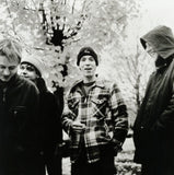 Black and white photograph of Jeff Mueller, Sean Meadows, Fred Erskine and Doug Scharin of June Of 44. In the photograph the band are stood outdoors in front of a tree with bright leaves. It must be cold because they are wearing coats and hats, but they appear cheerful.