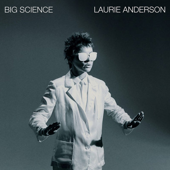Big Science by Laurie Anderson on Nonesuch Records (the album cover is a black and white photograph of Laurie Andeson in a white suit and white sunglasses stood with her hands out flat against a grey background; the album title and artist name are printed in a white uppercase sans-serif font across the top)
