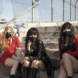 Photograph of L.A. Witch sitting outdoors on concrete steps. The three members of the band all are wearing face masks