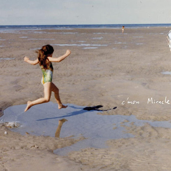 C'mon Miracle by Mirah on Double Double Whammy Records (the album cover is a colour photograph of a young girl in a bathing suit on a beach leaping across a puddle of water in the sand; the sea appears on the horizon in the background; the girl, with long dark hair, faces away from the camera; the album title in hand-written in white text midway down the right-hand side, against the sand on the photograph).