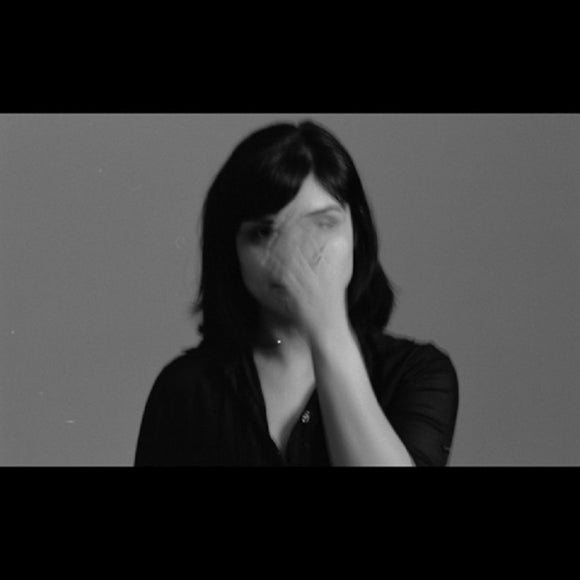 All My Circles Run by Sarah Davachi on Late Music (the album cover is a black and white photograph of Sarah Davachi by Alex Waber; Davachi's blurred hand obscures most of her face; the photograph is bordered on the top and bottom by solid black margins; there is no text on the image)