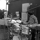 Black and white photograph showing Simeon and Dan Taylor of Silver Apples playing live outdoors as a small crowd look on