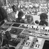 Black and white photograph of children looking at Silver Apples electronic equipment and smiling. The photograph is taken outdoors, and in the background is an audience of people sat down and stood up facing the band