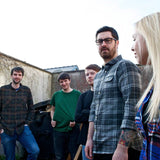 Photograph of Silverbacks; all five members of the band (Daniel O'Kelly, Kilian O'Kelly , Emma Hanlon, Peadar Kearney, and Gary Wickham) wear casual clothes and stand awkwardly