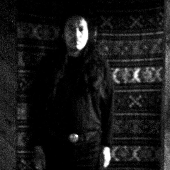 Stateless by Tashi Dorji on Drag City Records (the album cover depicts an grainy, dark, and out-of-focus black and white photograph of Tashi Dorji standing in front of a patterned wall hanging. There is no text on the front of the album sleeve)