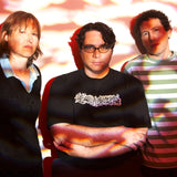 Band photograph Georgia Hubley, James McNew, and Ira Kaplan of Yo La Tengo. In the photograph, the band are stood against a wall, dappled in red-tinged light
