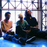Photograph of Ira Kaplan, Georgia Hubley, and James McNew of Yo La Tengo (the photograph shows the three members of the band sat on the floor, leaning against a railing by an industrial looking window; they are back-lit by the light coming through the window; they all appear content)