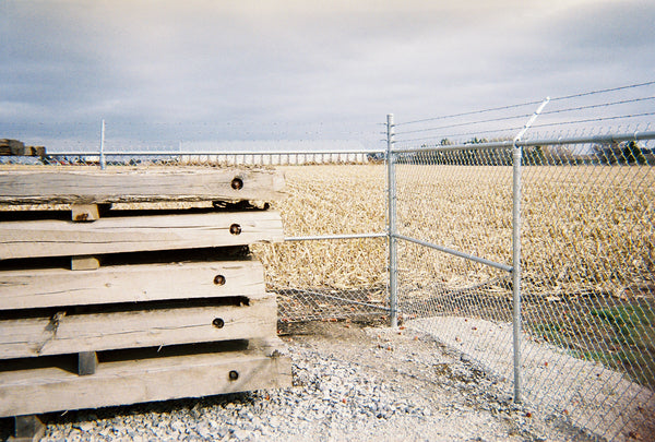 Some wood pallets stacked in front of the corner of a commercial chain link fence with barb wire running across the top