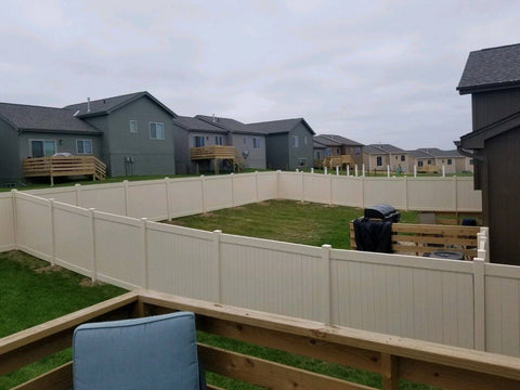 Neighboring white vinyl privacy fencing