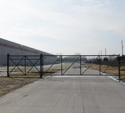 Black chain link cantilever gate installed in front of a large warehouse