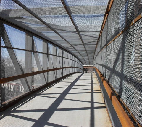 A walk bridge enclosed in commercial chain link fabric