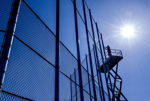 An American Fence Company employee installing chain link fabric to a 40-foot backstop while in a lift