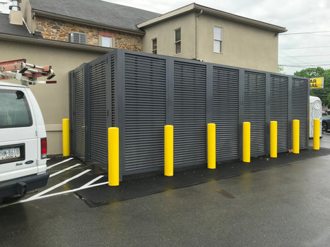 Bright yellow traffic control columns are installed in striking contrast in front of Mission Dispensary's horizontal louvered fencing from PalmSHIELD