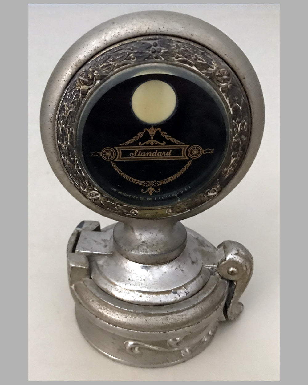 Large standard motometer by Boyce with attached revolving decorative hub cap