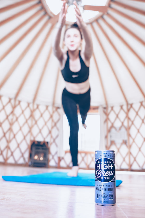 Woman doing yoga with a high brew cold brew can