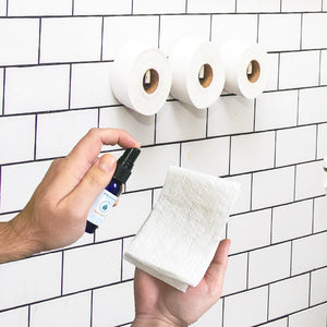 Pristine Sprays flushable wet wipe alternative being sprayed onto toilet paper by male hand in white bathroom, subway tile