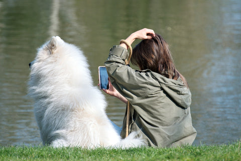 girl sitting with her dog on phone