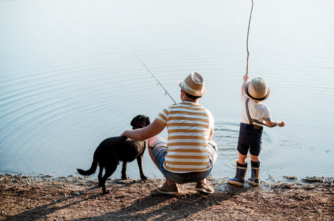 son and dad fishing with dog
