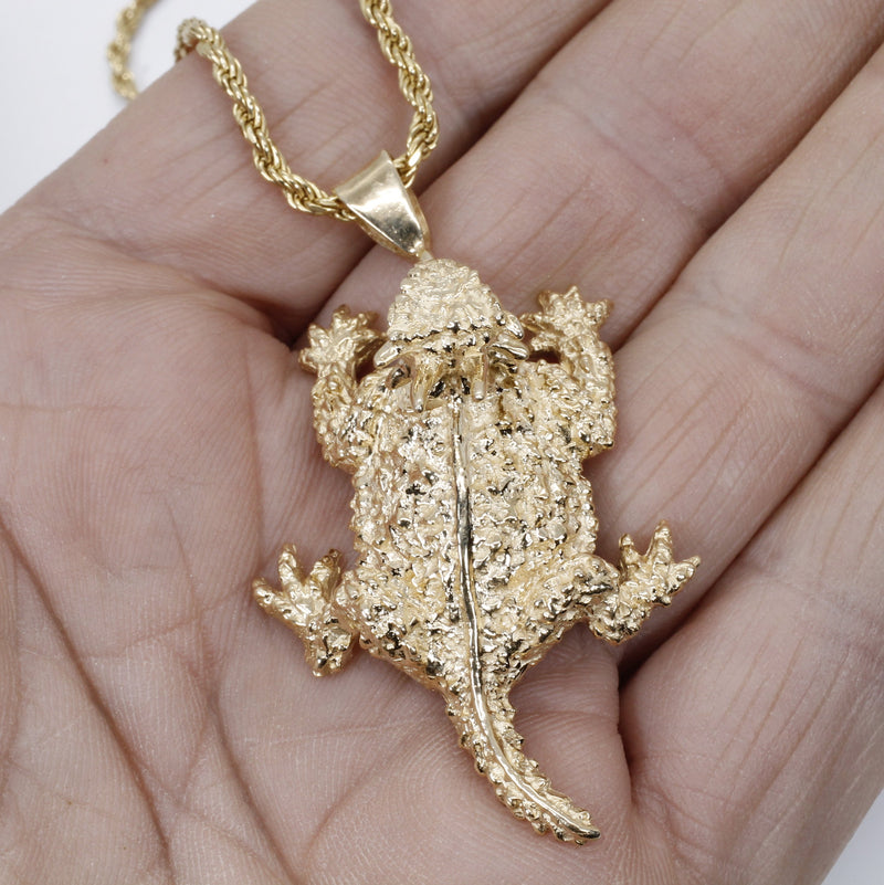 giant 14kt gold horned toad frog necklace shown on hand