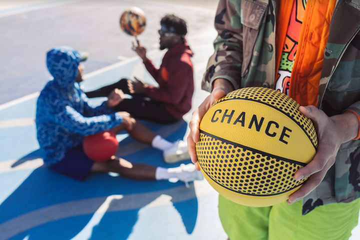 In foreground male hands holding a Chance basketball, in background 2 other men sitting on a basketball court waiting to begin basketball drills