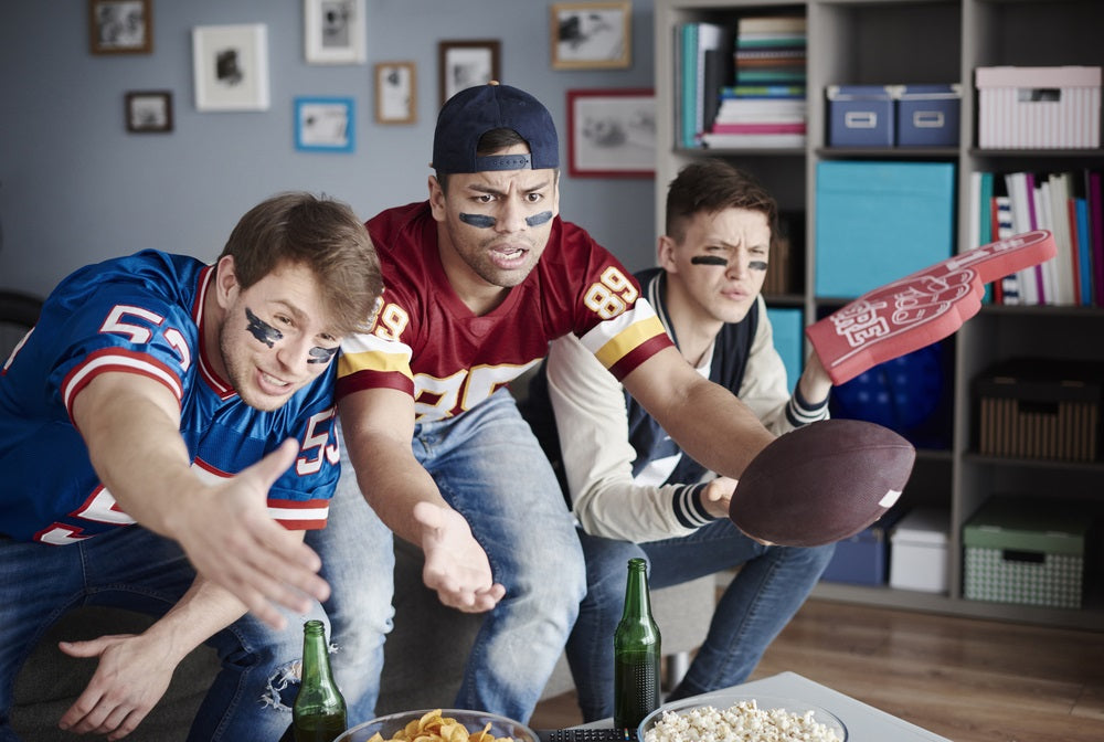 Unhappy men on sofa watching NFL draft 2018