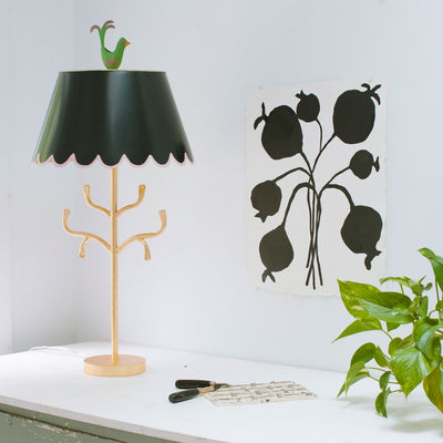 gold iron lamp with branches, black scalloped shade and green bird
