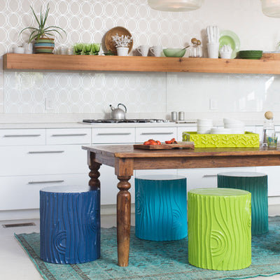 stump stools in a variety of greens and blues around a kitchen table