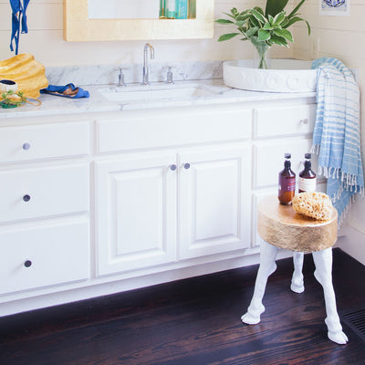 designer accent table with gold leaf in beach house bathroom