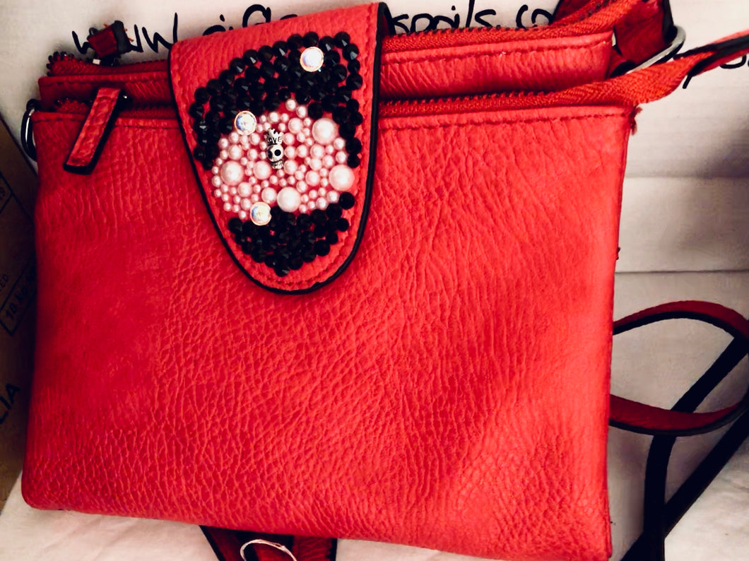 red bag with crystals and skull on the front, vegan leather