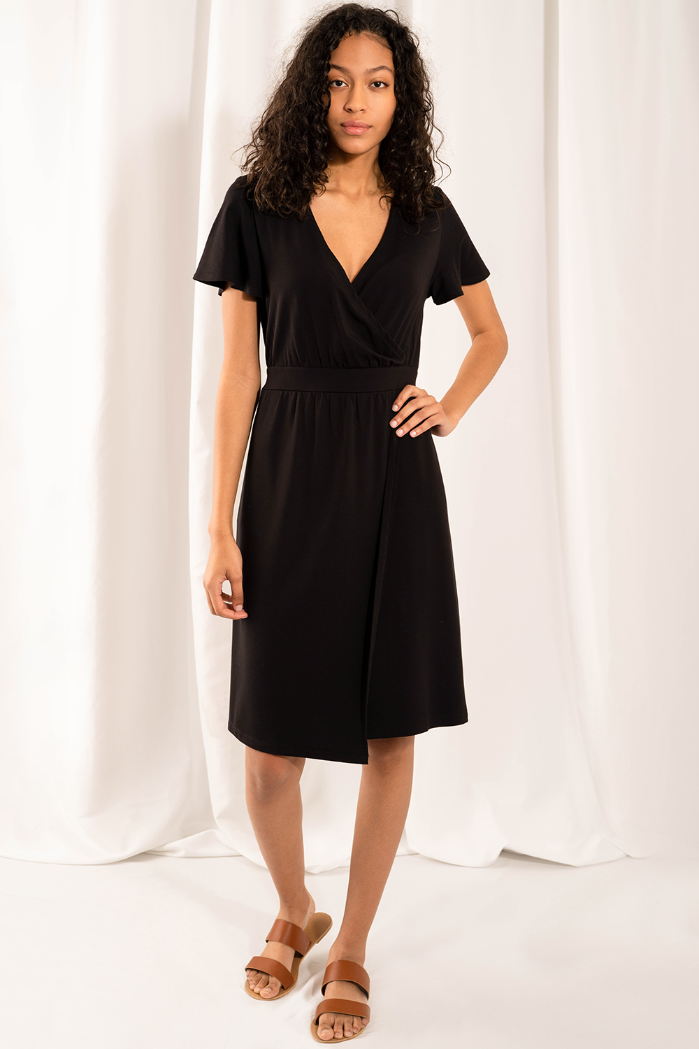 The elegant Taya Wrap Dress raises the bar on style and comfort. The fixed tie-waist detail means that you can easily slip the dress over your body! With sleeves for coverage, a flattering V-neck, and a side slit for movement, you will Love wearing this dress! Fabrication: 95% Viscose from bamboo, 5% Spandex   LNBF colour Black $95.00