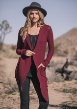 Go full hemp goddess in our first ever long knit cardigan in hemp and organic cotton. Two big slouch buttons on the pockets. Hooded, with an asymmetrical hem that is longer in front for a flowy vibe. Fabrication: 55% Hemp 45% Organic Cotton NOMADS Colour Cabernet Red