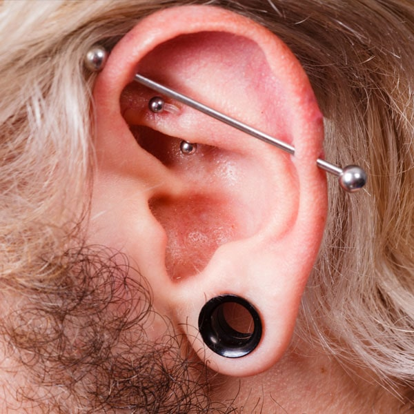 Man with industrial barbell piercing, rook piercing, and stretched earlobes