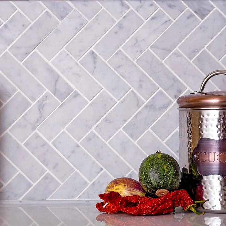 The Beauty of Natural Stone in an Affordable Kitchen Backsplash with Carrara Marble Herringbone Tiles