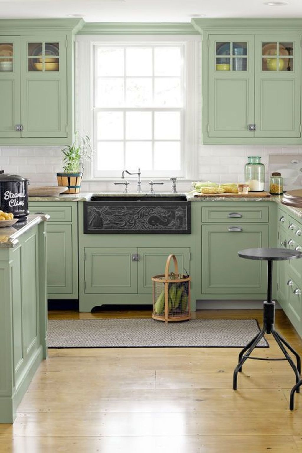 Thinking of a soothing green cabinet paint? This airy kitchen seen on Country Living makes for a relaxing space to cook, gather, and unwind with a glass of wine!