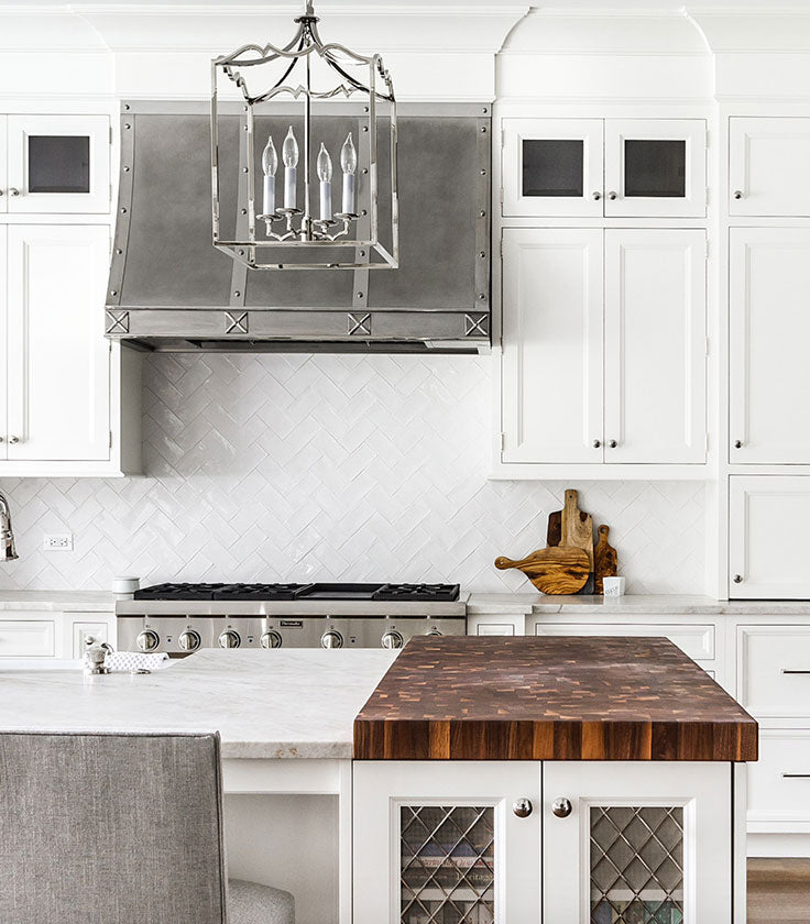 White Kitchen with Ceramic Subway Tile Behind the Stove with a Chevron Pattern