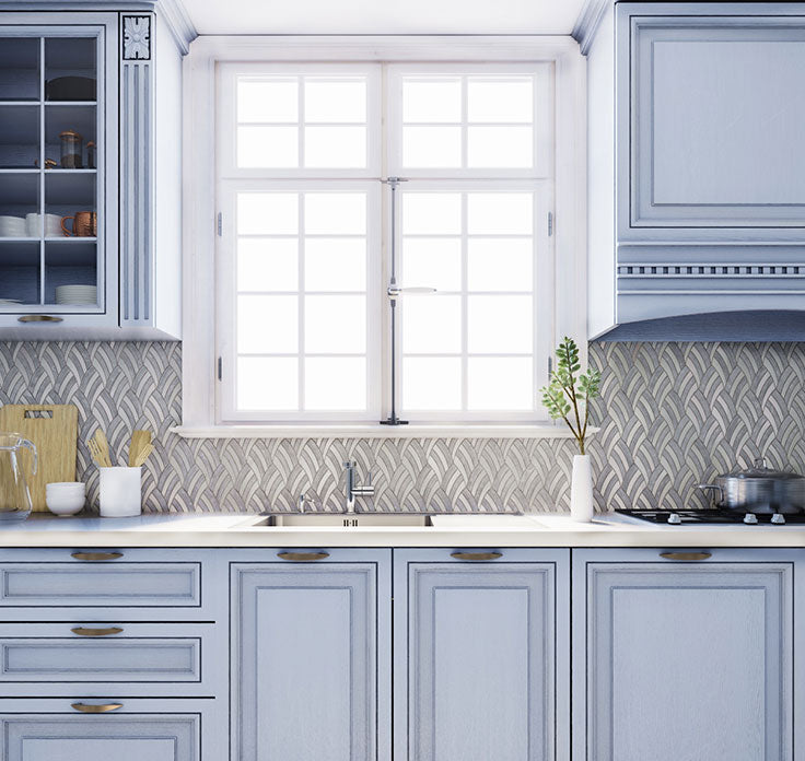 Decorative marble tiles give this blue and white kitchen a patterned backsplash