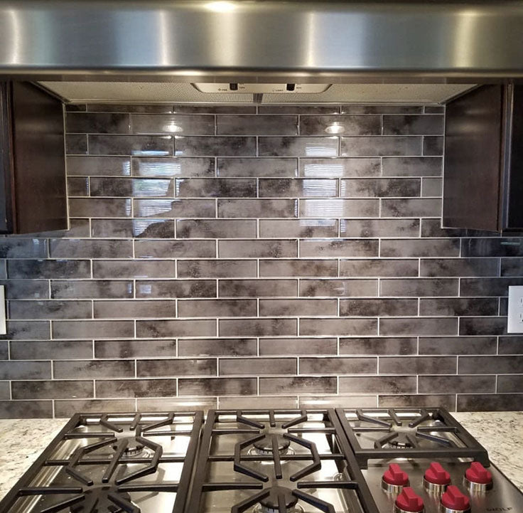 Textured Glass Subway Tiles add Color and Depth on the Backsplash Behind the Stove