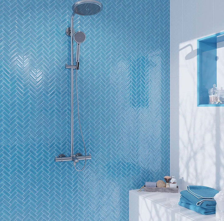 This serene blue and white shower with a herringbone glass tile wall adds Mediterranean style