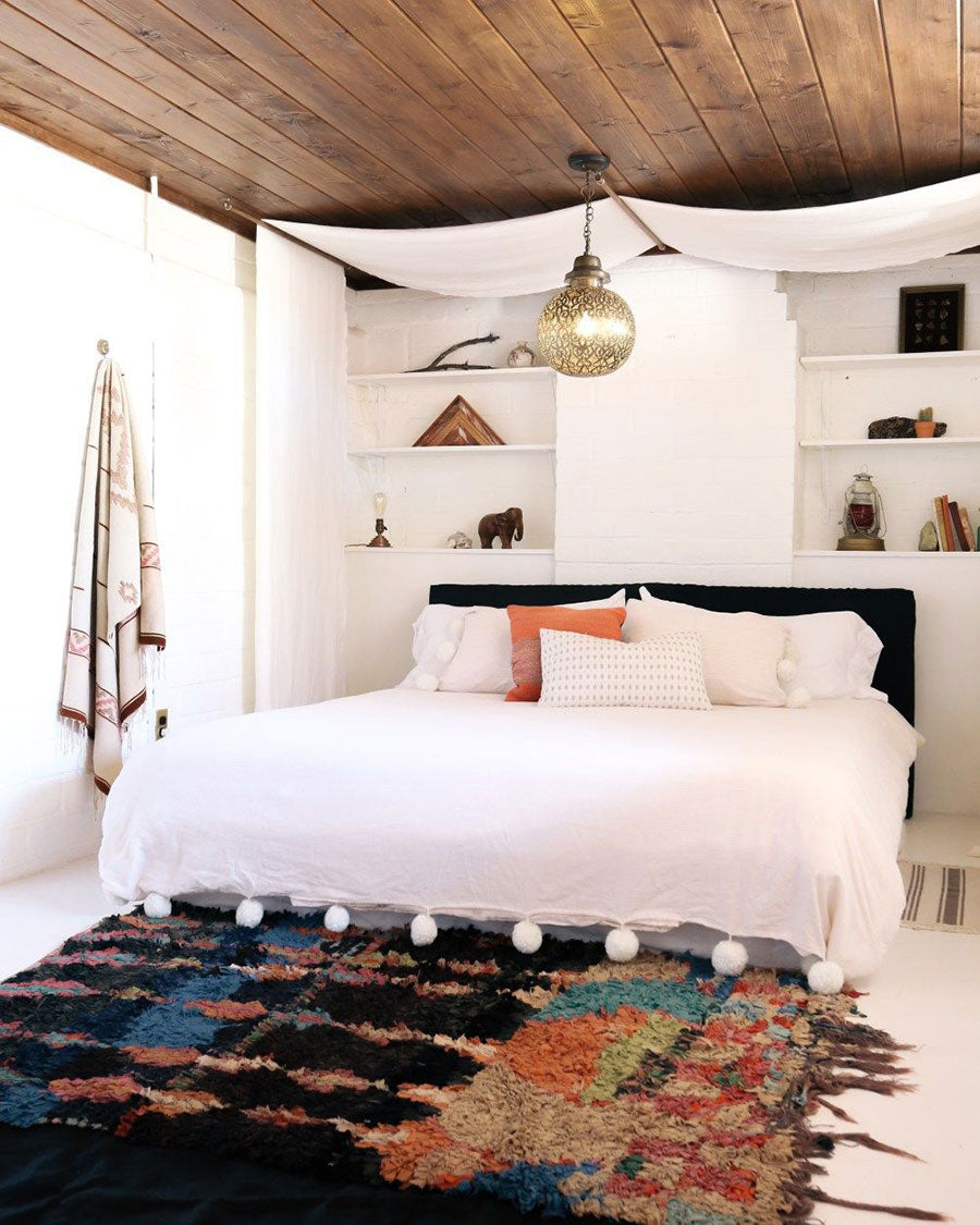 This bedroom embraces the bohemian atmosphere of Joshua Tree to create a 'treehouse' atmosphere. It's thoughtfully designed with accents that give the space an extra pop of color, pattern and a lovely warmth and add to the Southern California meets Southwest flavor of the desert rental house