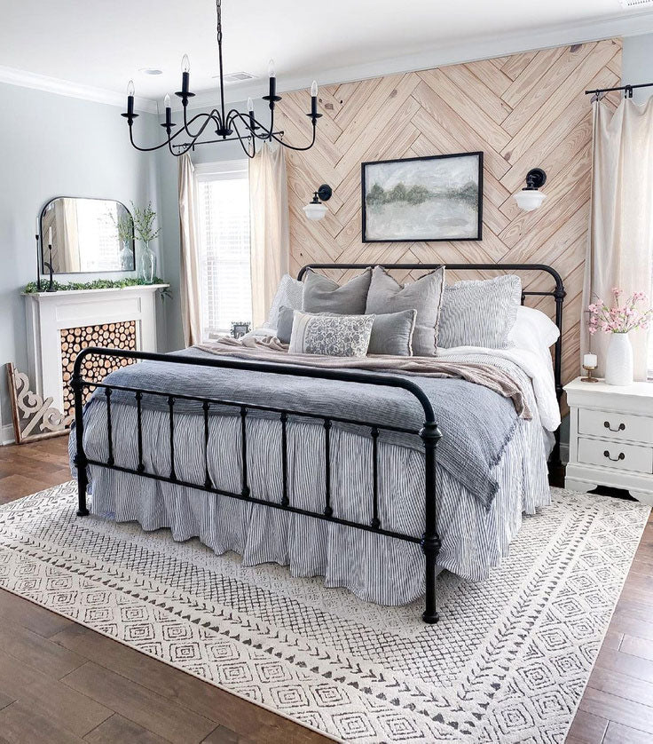 The Aztec patterned area rug from Ruggable under the cast iron bed frame adds a  Black and white patterned touch to the cool gray bedding and the stunning herringbone accent wall!