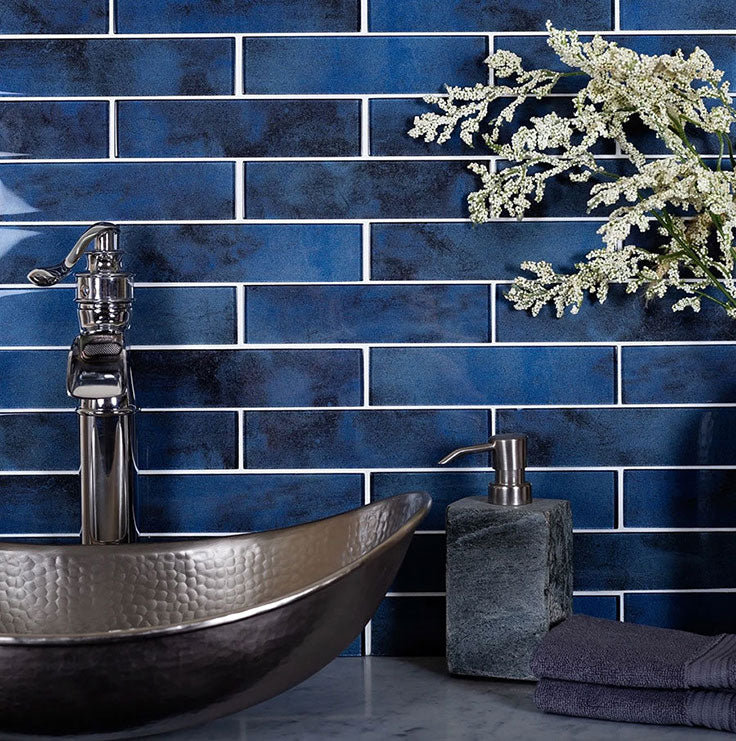 Saturated colors from glass subway tiles add rich blue to a modern bathroom design