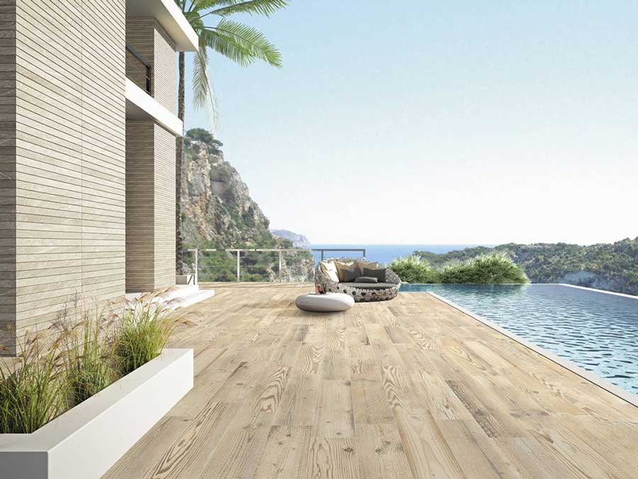 This wood look Tribeca Miel porcelain pool deck is a seamless transition from the pool tile to the coping as a sturdy outdoor tile option!