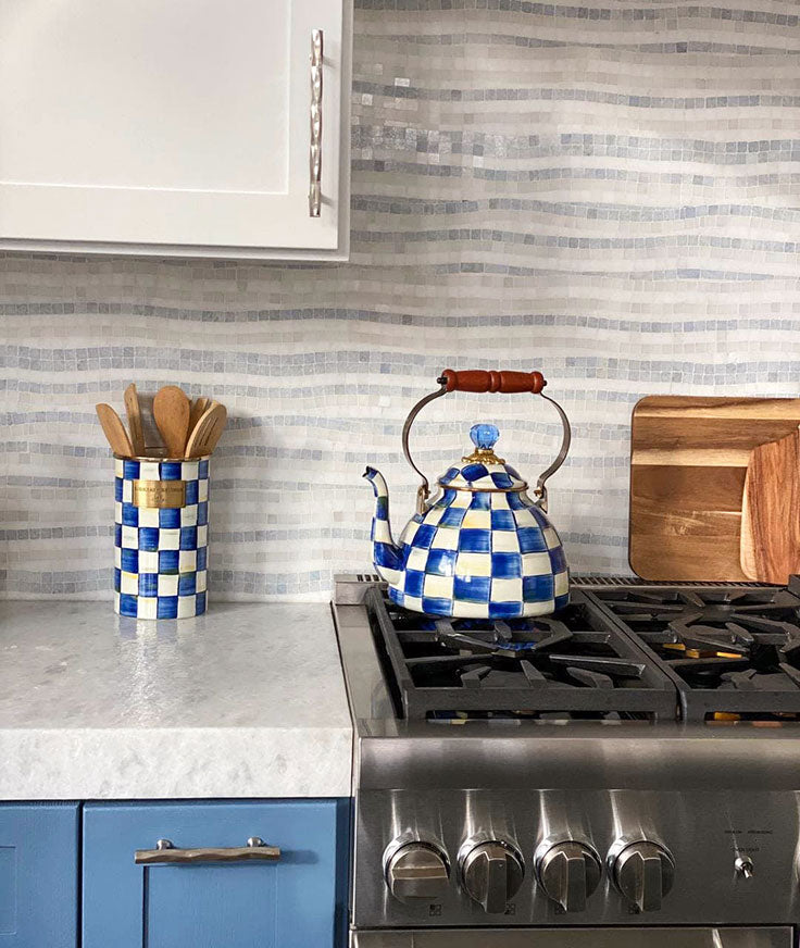 Leathered marble countertop with a raw edge adds stunning texture to a chic white and blue kitchen design